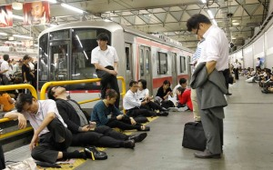 Passengers wait for the resumption of train service after it was halted by Typhoon Roke, at Shibuya station in Tokyo